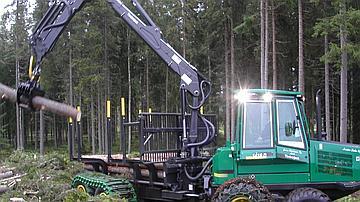 Ce tracteur articulé limite la pression au sol grâce à quatre essieux munis de pneux basse pression et de chenilles