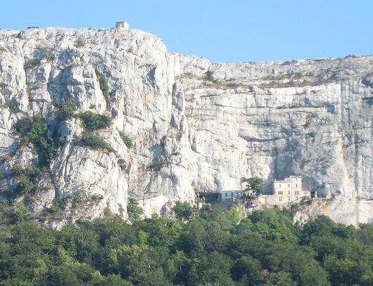 Photo de l'netrée de la grotte au pied de la falaise